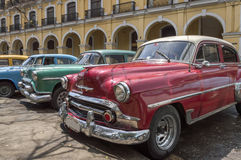 American classic cars parked in Havana. A series of old american cars from the 50's, parked in Havana, Cuba in front of a yellow colonial building royalty free stock image