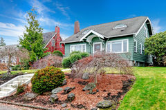 American classic house esterior. Curb appeal idea. Green clapboard house with tile roof. Beautiful landscaping idea Royalty Free Stock Image