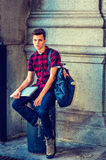 American College Student relaxing on street in New York. College Student. Dressing in a short sleeve, black, red patterned shirt, jeans, boot shoes, carrying a Stock Image