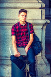 American College Student relaxing on street in New York. College Student. Dressing in short sleeve, black, red patterned shirt, jeans, carrying shoulder bag Royalty Free Stock Images