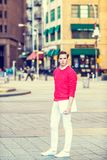 American college student studying in New York,. Wearing red knit sweater, white pants, shoes, holding laptop computer, standing on street, confidently looking Stock Photo