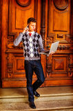 American College Student Studying, Working in New York. Busy Student. Wearing a patterned sweater, red tie, blue jeans, leather shoes, a young guy is walking Stock Photography