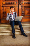 American College Student Studying, Working in New York. Man Working Hard. Wearing a patterned sweater, red tie, blue jeans, leather shoes, a young guy is sitting Royalty Free Stock Photo