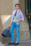 American college student traveling, working in New York,. Wearing sleeveless hoodie, long sleeve, pink shirt, necktie, jeans, leather shoes, holding laptop Royalty Free Stock Photography