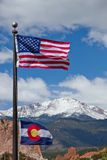 American and Colorado Flag waving in the wind with mountains in. American and Colorado Flag waving in the wind with Pikes Peak and Garden of the Gods in the stock image