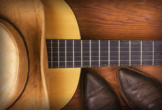 American Country music background with cowboy boots. American Country music with guitar and cowboy shoes on wood background Royalty Free Stock Image