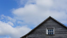 American Countryside Sky. A blue sky with off-white clouds above an old american style wooden house Royalty Free Stock Photos