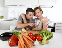 American couple in domestic kitchen wife following recipe in digital pad working together with husband Stock Photos
