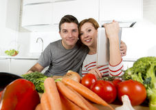 American couple in domestic kitchen wife following recipe in digital pad working together with husband Stock Photography
