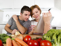 American couple in domestic kitchen wife following recipe in digital pad working together with husband Stock Photo