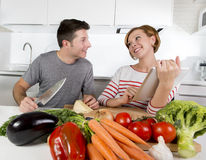 American couple in domestic kitchen wife following recipe in digital pad working together with husband Royalty Free Stock Image