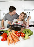 American couple at home kitchen smiling happy together wife cooking husband tasting the vegetable stew Stock Photo