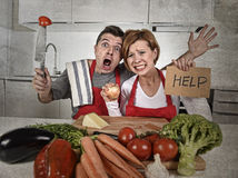 American couple in stress at home kitchen in cooking apron asking for help frustrated Stock Image