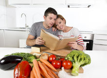 American couple working in domestic kitchen following recipe reading cookbook together. Young happy American couple working in domestic kitchen, following recipe Royalty Free Stock Photography