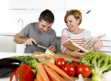 American couple working in domestic kitchen together wife following recipe in cookbook and husband slicing cheese Stock Images