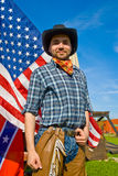 American Cowboy. Man in authentic American cowboy outfit, with the USA flag in the background royalty free stock photo