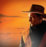 American cowboy in hat. American cowboy in brown hat on a sunset background outdoor stock photography
