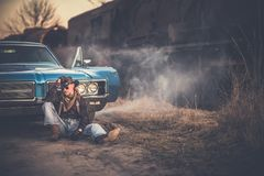 The American Cowboy Story. Caucasian Men Wearing Western Style Clothes and Cowboy Hat, Taking a Moment in Front of His American Classic Muscle Car. Aged and stock photography
