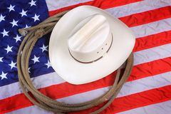 American Cowboy Symbol. A white straw cowboy hat and rope laying on an American flag background. Symbol concept Stock Image
