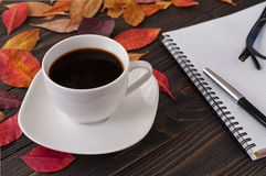 American cup of coffee with fallen autumn leaves and notebook Stock Photos