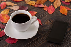 American cup of coffee with fallen autumn leaves and smartphone Royalty Free Stock Photography