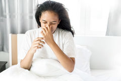 The american cute girl sick and sneeze on white bed. American cute girl sick and sneeze on white bed Stock Image