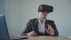 American designer get virtual experience using vr glasses at table with laptop in office. Front of young businessman researching cyber virtual space, wearing stock video