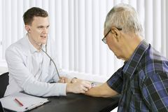 American doctor examines elderly man heartbeats. Picture of American male doctor examining elderly men heartbeats by using a stethoscope in the clinic Stock Images