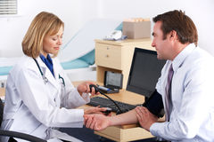 American doctor taking patient's blood pressure Royalty Free Stock Images