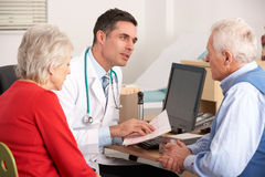 American doctor talking to senior couple stock photo