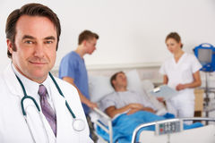 American doctor and team on hospital ward. Smiling at camera with student doctors tending to patient in background Stock Photography