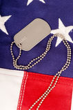 American Dog Tags. A lone dog tag sits on top of an American Flag Stock Photography