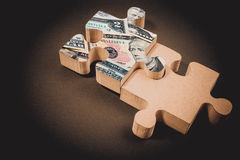 American dollar banknote over jigsaw puzzle with copy space. Stock Photo
