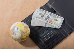 American dollar banknotes by a globe and calculator royalty free stock photography
