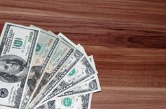 American dollar banknotes laid out in a corner. On the wooden background royalty free stock photography