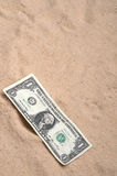 An American dollar bill on the sand Stock Photo