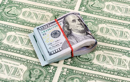 American dollar bills wrapped by rubber band over dollars Stock Photos