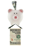 American 100 dollar currency in pink piggy bank standing on hous Royalty Free Stock Photos