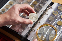 American dollar in hands of numismatist. And magnifying glass Royalty Free Stock Photos
