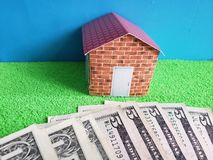 American dollars banknotes, figure of a house on green surface and blue background. Backdrop for mortgage and housing value ads, loan for home construction and stock photos