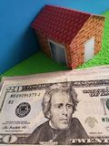 American dollars banknotes, figure of a house on green surface and blue background. Backdrop for mortgage and housing value ads, loan for home construction and royalty free stock photos