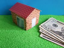 american dollars banknotes, figure of a house on green surface and blue background