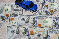 American dollars and a blue toy car on a wooden table royalty free stock images