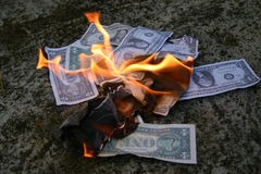 Money to burn. American dollars burning on the pavement with flames in the centre Royalty Free Stock Photos