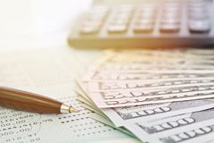 American Dollars cash money, calculator and savings account passbook or financial statement on table. Business, finance, investment, savings or accounting Stock Photography