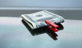 American dollars are clamped with a red clothespin. American dollars clamped with a red clothespin on a mirror surface Royalty Free Stock Images