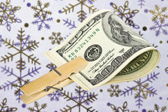 American dollars with a clothespin on the background of snowflak Stock Photo
