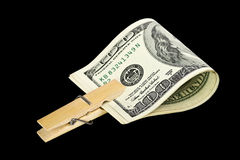 American dollars with  clothespin. American dollars with with a wooden clothespin on black background Royalty Free Stock Photos