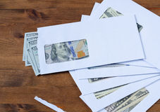 American dollars in the envelopes. On wooden table Stock Images
