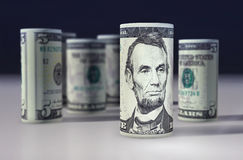 American 5 dollars greenback rolled up on the black.  Stock Photo